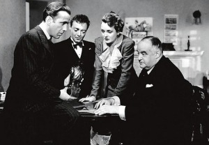 Humphrey Bogart as Sam Spade, with Peter Lorre, Mary Astor and Sydney Greenstreet looking on in John Huston's The Maltese Falcon (1941)